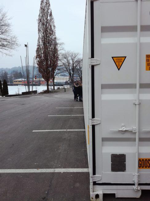 Eine Schulklasse steht am Ende eines langen Schiff-Containers. Einige Schüler*innen betreten den Container.
