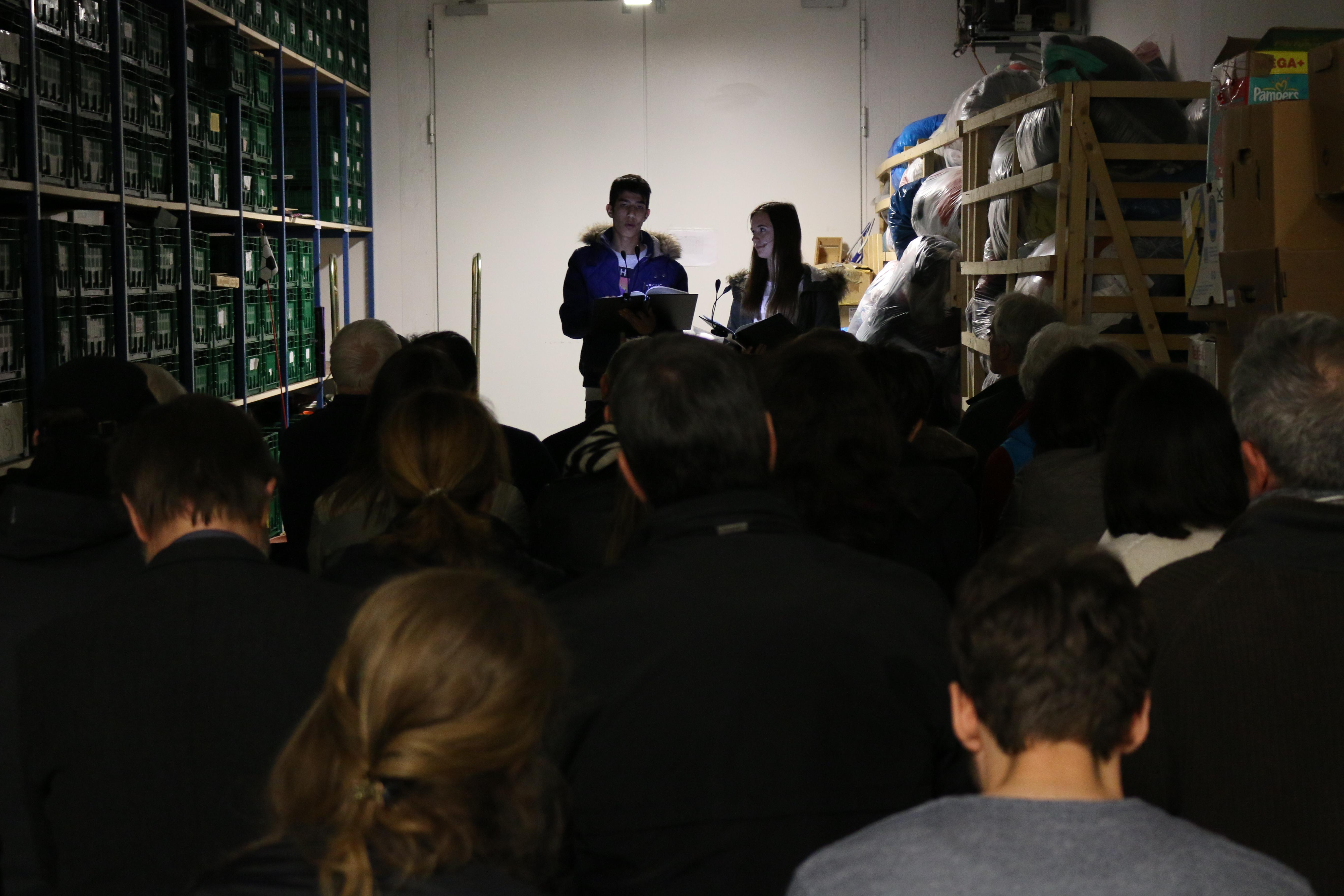 Zwei Schauspielende lesen eine Geschichte vor Publikum. Im Raum ist nur wenig Licht und es ist eng.