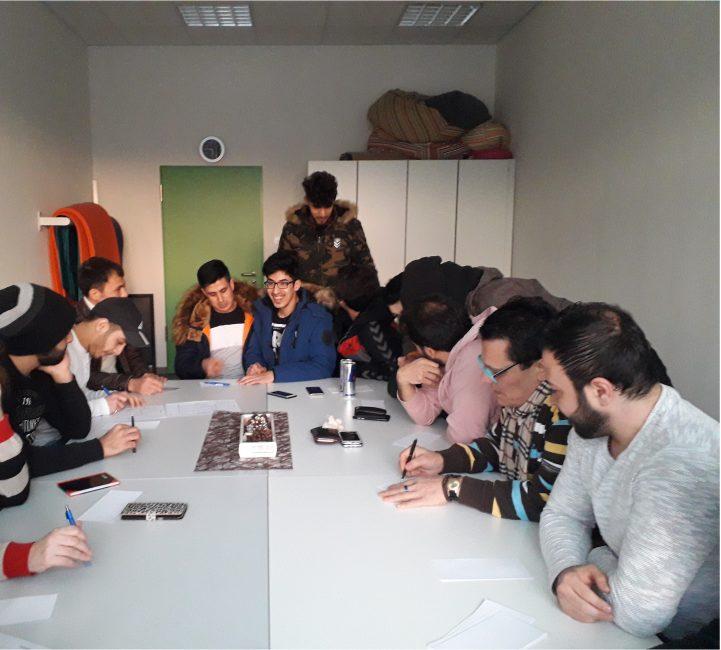 Eine Arbeitsgruppe aus Jugendlichen und jungen Erwachsenen sitzen an einem großen Tisch und beraten sich.