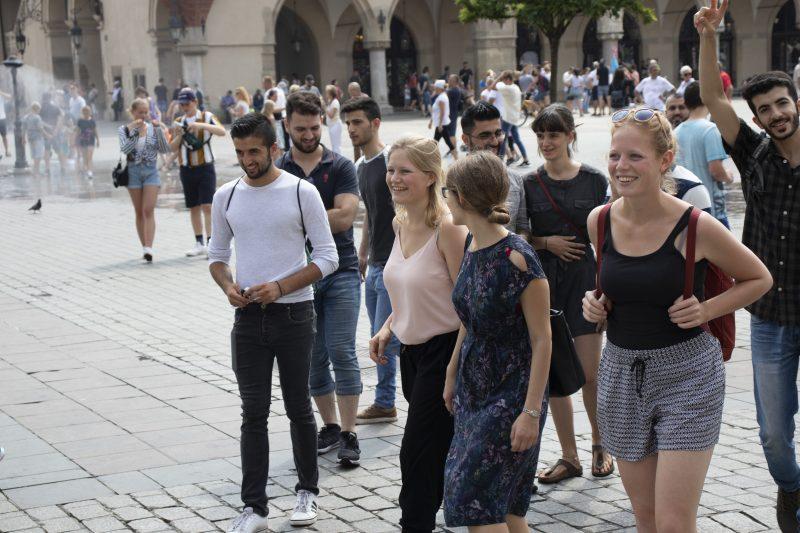 Die Teilnehmenden der Reise laufen über einen großen Platz in Krakau.