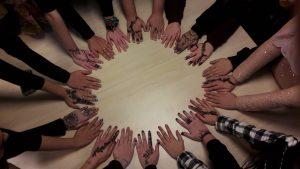 Teilnehmende zeigen ihre mit unterschiedlichen Mustern bemalten Hände.