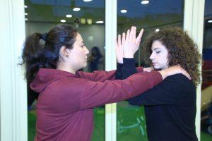 Zwei junge Frauen üben die Selbstverteidigung.