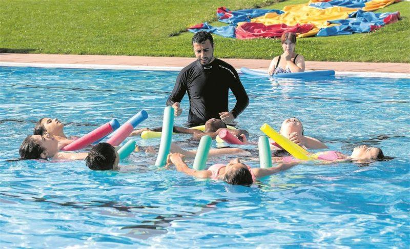Eine Gruppe Kinder übt gemeinsam mit dem Schwimmlehrer im Freibad. Alle haben Schwimmnudeln bei sich.