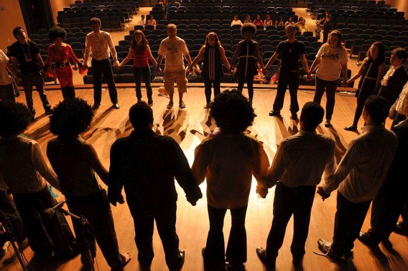 EIne Theatergruppe, bestehend aus Jugendlichen, steht in einem großen Kreis auf der Bühne. Sie halten sich an den Händen und proben.