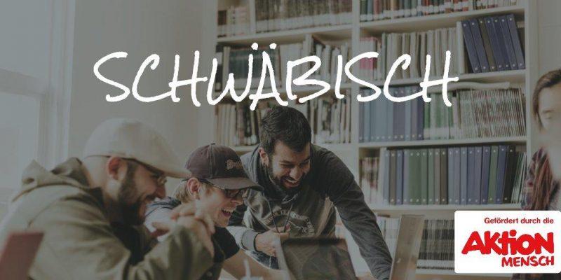 """Eine Gruppe Jugendliche sitzt in einer Bücherrei und lacht gemeinsam. Auf dem Bild steht in Handschrift das Wort """"Schwäbisch"""" geschrieben."""