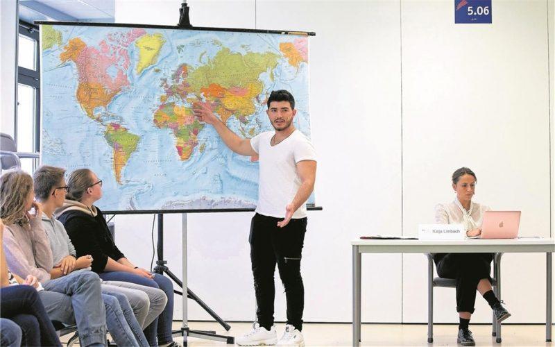 Ein Jugendlicher zeigt der Schulklasse auf einer großen Landkarte sein Herkunftsland