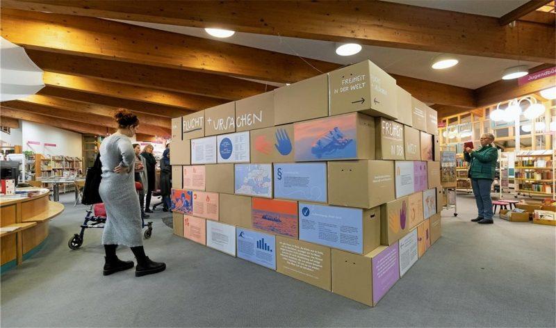 Besucher*innen laufen durch die Ausstellung in der Bücherrei. Im Zentrum steht eine Wand aus bedruckten Kartons.