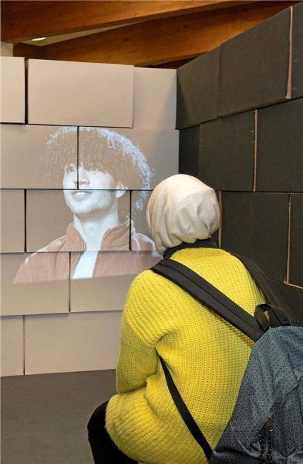 Eine Frau sitzt vor einer Leinwand, auf welcher ein Jugendlicher von seiner Flucht erzählt.