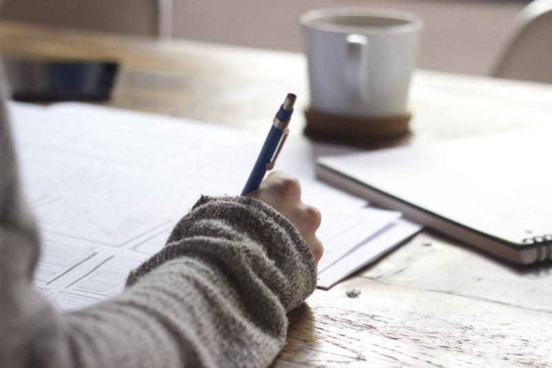Eine Person sitzt an einem Schreibtisch und arbeitet über einem Stapel mit Papieren.