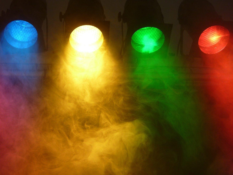 4 große Scheinwerfer in einer Reihe. Sie haben die Farben blau, gelb, grün und rot.